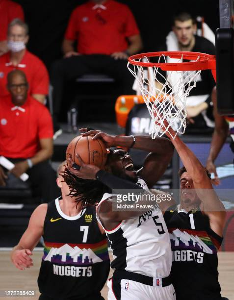 Montrezl Harrell of the LA Clippers drives to the basket over Mason Plumlee of the Denver Nuggets and Michael Porter Jr #1 of the Denver Nuggets...
