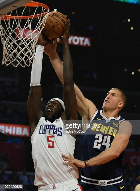 Montrezl Harrell of the LA Clippers gets past Mason Plumlee of the Denver Nuggets in the first half during the season opening game at Staples Center...