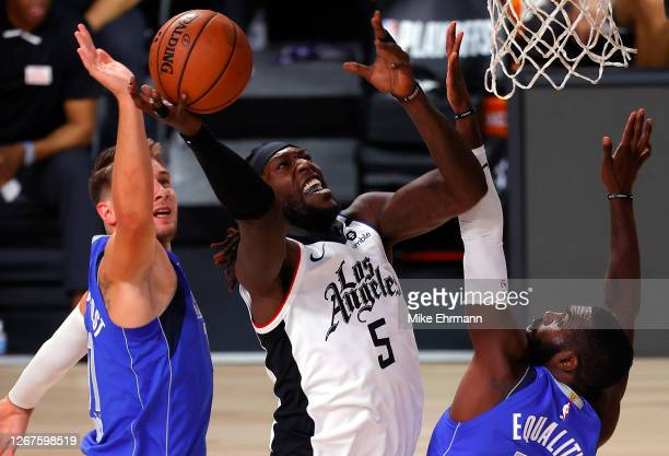 Montrezl Harrell of the LA Clippers goes up for a shot against Luka Doncic and Tim Hardaway Jr of the Dallas Mavericks during the first quarter in...