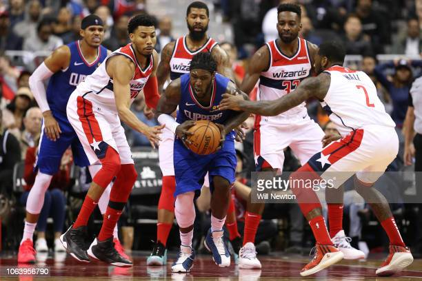 Montrezl Harrell of the LA Clippers is pressured by Otto Porter Jr #22 and John Wall of the Washington Wizards during the second half at Capital One...
