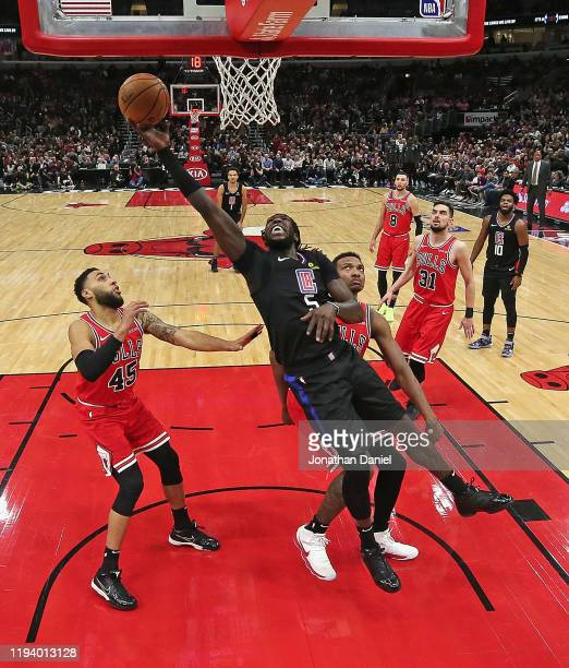 Montrezl Harrell of the LA Clippers lays in a shot between Denzel Valentine and Wendell Carter Jr #34 of the Chicago Bulls at the United Center on...