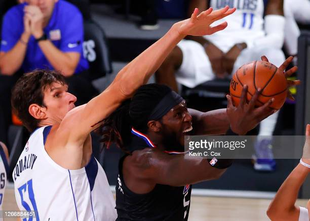 Montrezl Harrell of the LA Clippers makes a basket against Boban Marjanovic of the Dallas Mavericks during the third quarter in Game One of the...