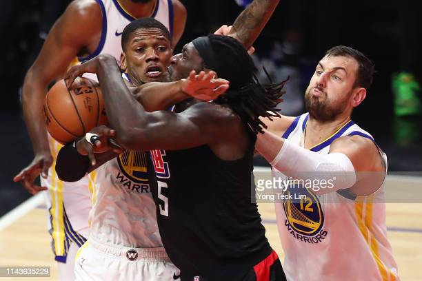 Montrezl Harrell of the Los Angeles Clippers is fouled on a drive to the basket by Alfonzo McKinnie of the Golden State Warriors during the first...