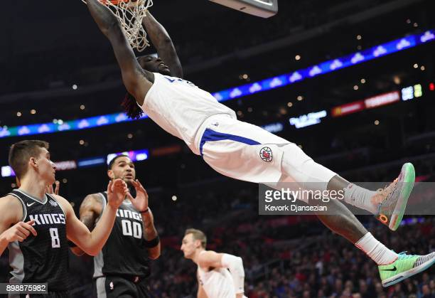 Montrezl Harrell of the Los Angeles Clippers slam dunks against Bogdan Bogdanovic and Willie CauleyStein of the Sacramento Kings during the second...