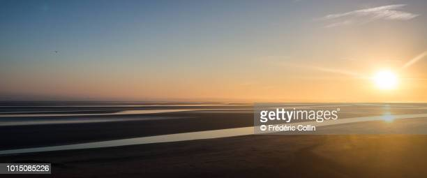mont-saint-michel at sunrise - zonlicht stockfoto's en -beelden