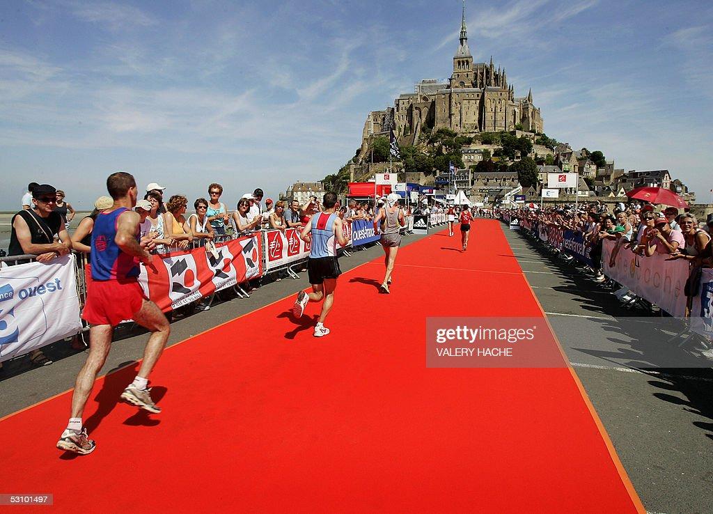 Marathon competitors run in front of Mont-Saint-Michel during the eight edition of the Mont-Saint-Michel Marathon, 19 June 2005 in French Normandy. Kenyan Patrick Chumba won the men's race and French Corinne Raux won the women's race.