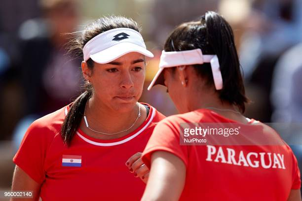 Montserrat Gonzalez of Paraguay talks with her teammate Veronica Cepede in their doubles match against Georgina Garca Perez and Maria Jose Martnez of...