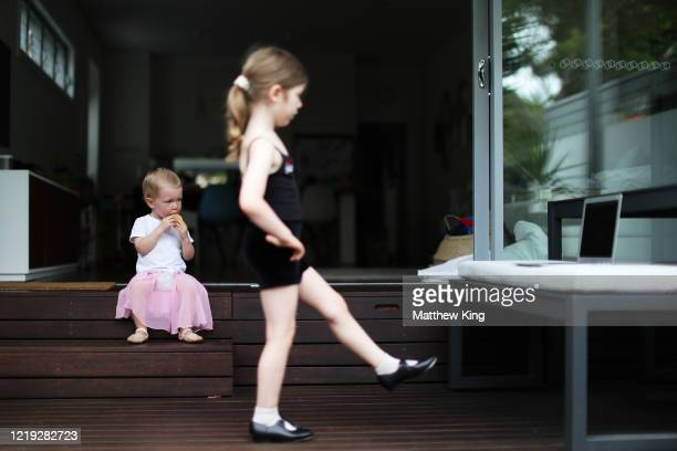 Monty King son of photographer Matt King is seen watching on as his sister Polly King takes part in an online ballet class in her home on March 28...
