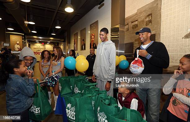 Monty Williams of the New Orleans Hornets and Anthony Davis distribute Thanksgiving baskets provided by the Hornets and Rouses to Emerge students on...