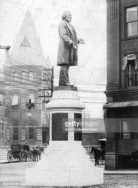Monument built to honor Frederick Douglass, a statue of Douglass stands on top of a stone base that contains several plaques of text, masonry...