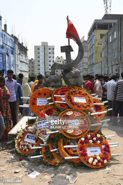 A monument for victims of the Rana Plaza building collapse is covered with floral wreath as people mark the sixth anniversary of the disaster at the...