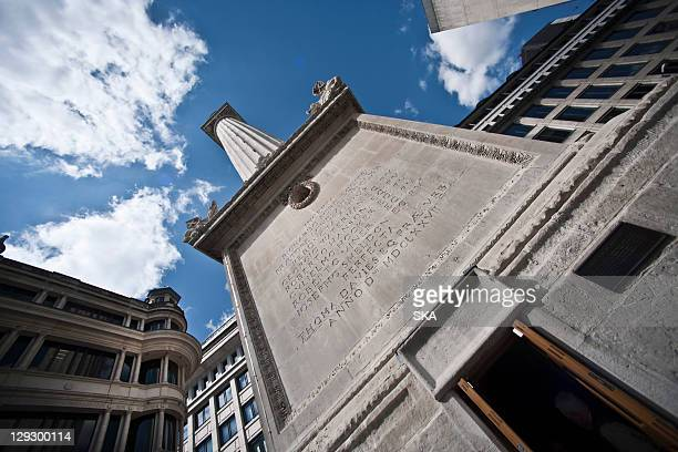 monument on city street against blue sky - great fire of london stock photos and pictures