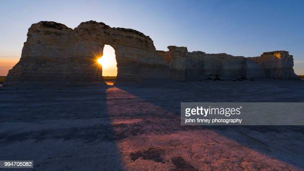monument rocks sunset through the arch, kansas - kansas stock pictures, royalty-free photos & images