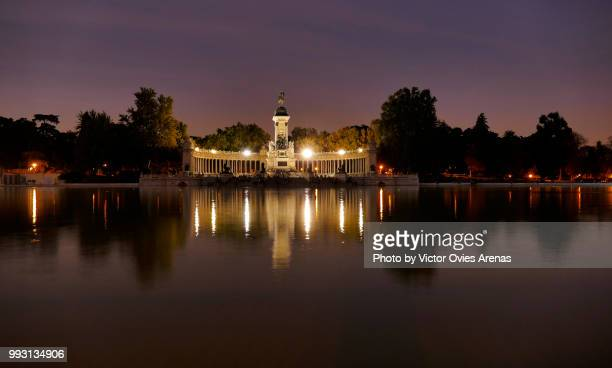 monument to alfonso xii and pond in the buen retiro park (parque del buen retiro) lit at twilight in madrid, spain - victor ovies fotografías e imágenes de stock