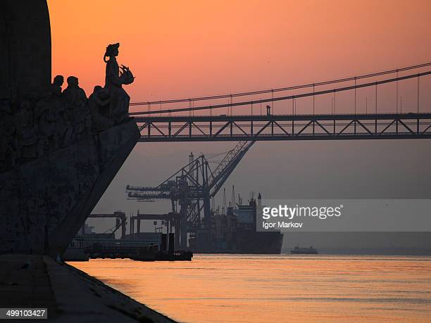 Monument to the Discoveries and Bridge 25 April alongside Tagus river in Lisbon, Portugal.