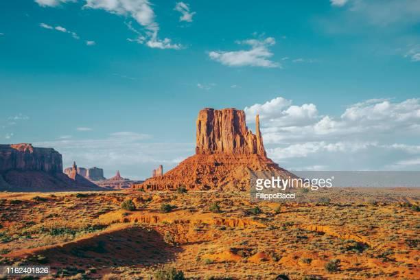 monument valley an einem sonnigen tag - größere sehenswürdigkeit stock-fotos und bilder