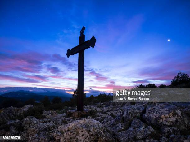 Monument with a great cross of iron on the top of a mountain, sky with crepuscular light to the dawn with the moon and some stars. Natural park of the Sierra Mariola in Bocairent, Natural park of the Sierra Mariola in Bocairent, Valencia, Spain.