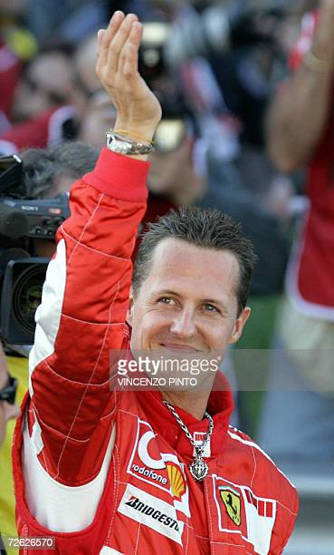 Picture taken 29 October 2006 shows German Ferrari driver Michael Schumacher waving to fans during the Ferrari exhibition at F1 race track in Monza....