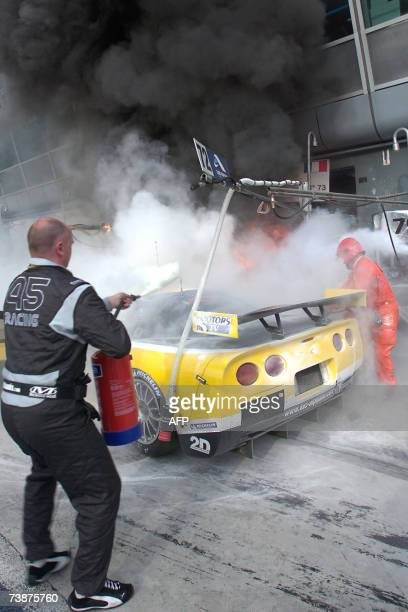 Two mechanics attempt to put out the fire in the pits of the Corvette of Belgian driver Vincent Vosse of Luc Alphand Adventures team during the...