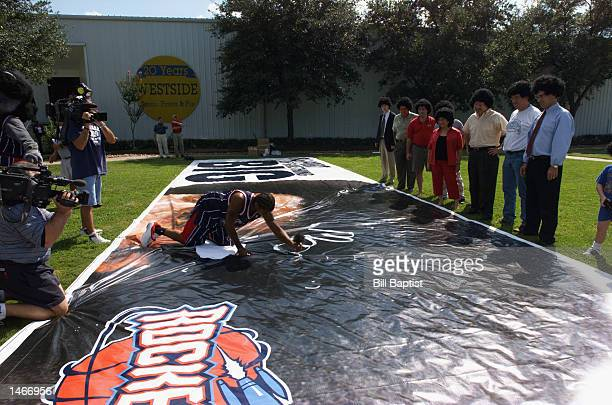 Moochie Norris of the Houston Rockets is watched by fans wearing Moochie Norris afro wigs as he signs a billboard during the Rockets Media Day on...
