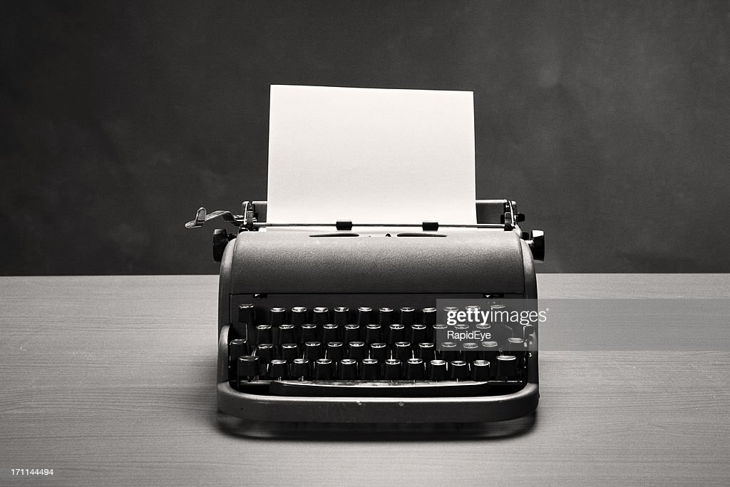 Moody film noir shot of vintage typewriter and blank paper : Stock Photo