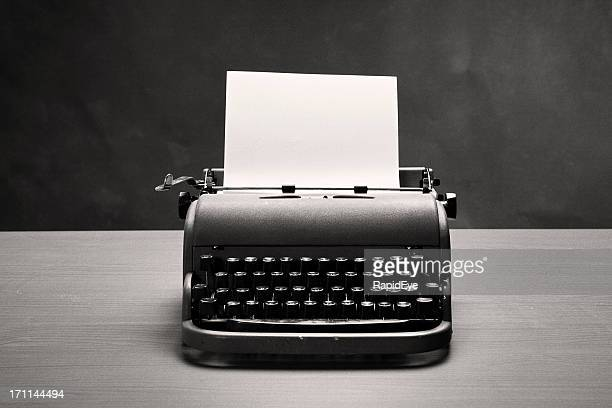 Moody film noir shot of vintage typewriter and blank paper