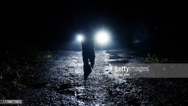 a moody hooded figure at night kneeling in front of car headlights with his hand up. as heavy rain comes down. - hooded top stock pictures, royalty-free photos & images