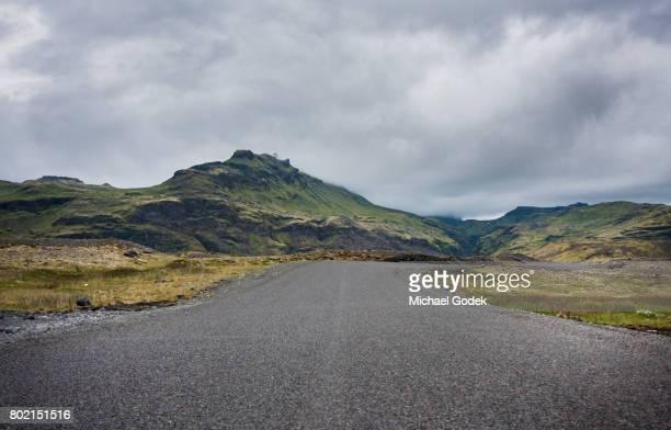 Moody image of empty road leading into the mountains near Iceland glacier