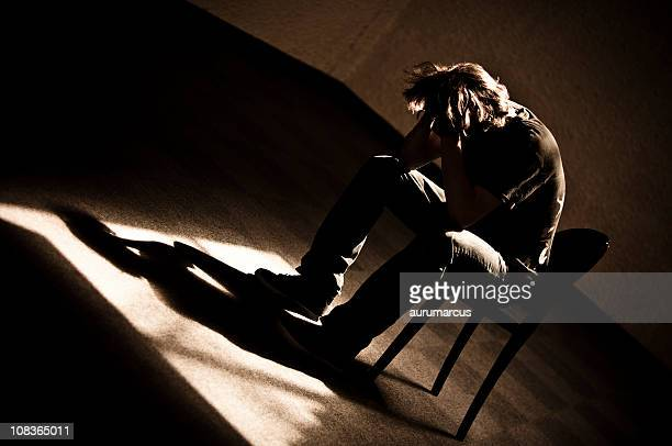 moody monotone shot of a depressed person slumped in chair - enslaved stock pictures, royalty-free photos & images