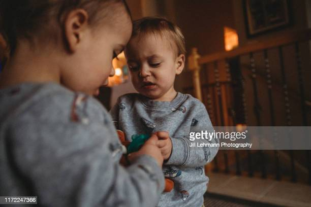 moody portrait fraternal twin toddlers (2 years) playing at home - 2 3 years stock pictures, royalty-free photos & images