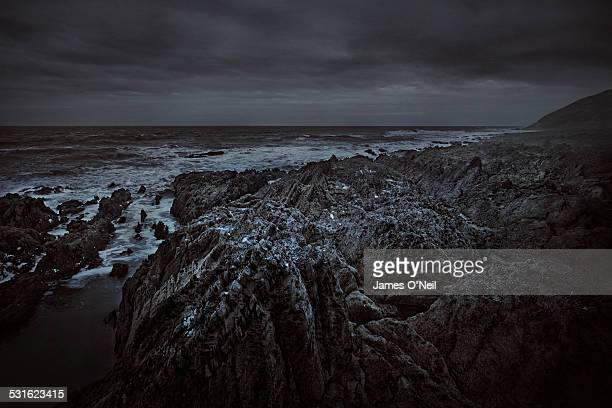 moody seascape with foreground rocks