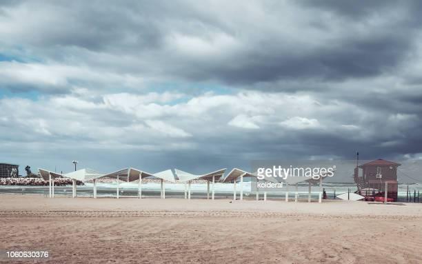 moody sky above mediterranean beach - 防波堤 ストックフォトと画像
