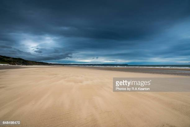 Moody sky over a wide open beach