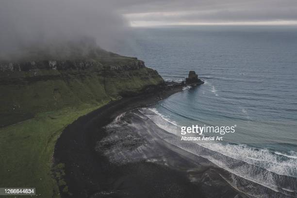 moody view showing coastline and black sand beach photographed by drone, isle of skye, scotland, united kingdom - dramatic landscape stock pictures, royalty-free photos & images