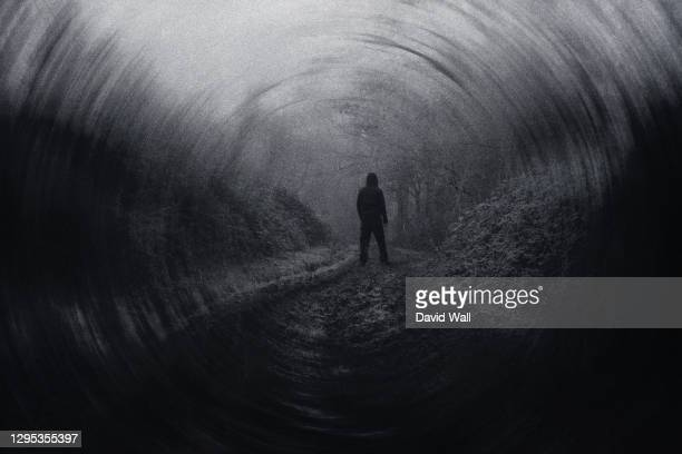 a moody winters day with a figure standing on a country path. with an abstract, blurred artistic edit. - winter stock pictures, royalty-free photos & images