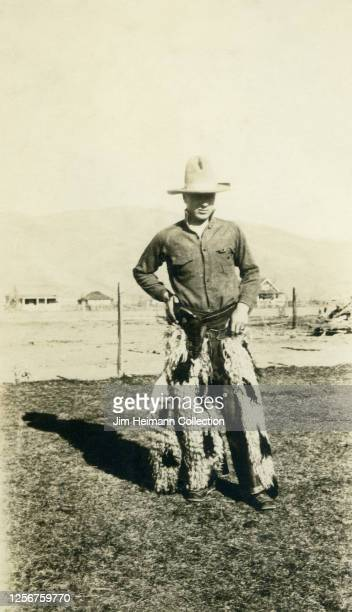 Moody young man dressed as a cowboy in sheepskin chaps, ahat, and gun holster poses for picture in a field, circa 1935.