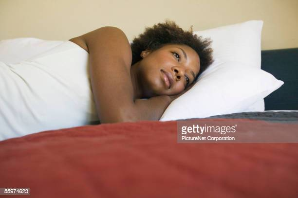 Moody young woman resting on her bed