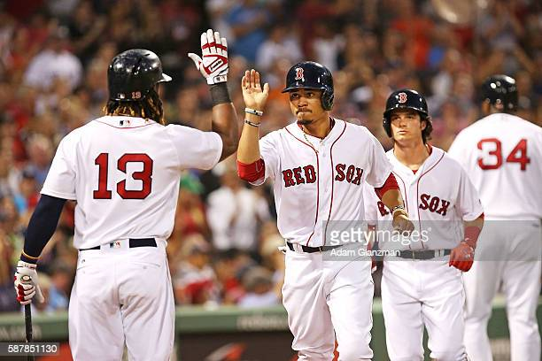 Mookie Betts and Andrew Benintendi high five Hanley Ramirez of the Boston Red Sox after scoring in the third inning of the game against the New York...