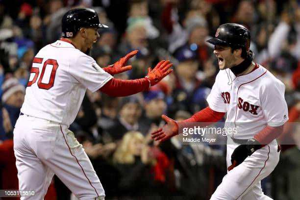 Mookie Betts and Andrew Benintendi of the Boston Red Sox celebrate each scoring a run on a hit by teammate JD Martinez during the fifth inning...