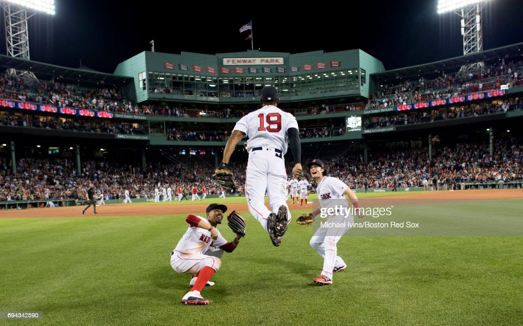 Mookie Betts #50 and Andrew Benintendi #16 react as Jackie Bradley Jr. #19 does the 'ski jump' to celebrate his ninth inning home run and a 5-3 win over the Detroit Tigers at Fenway Park on June 9, 2017 in Boston, Massachusetts.