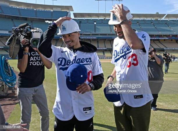 Mookie Betts and David Price of the Los Angeles Dodgers put on hard hats as they go on a tour of the new outfield pavilion construction after an...