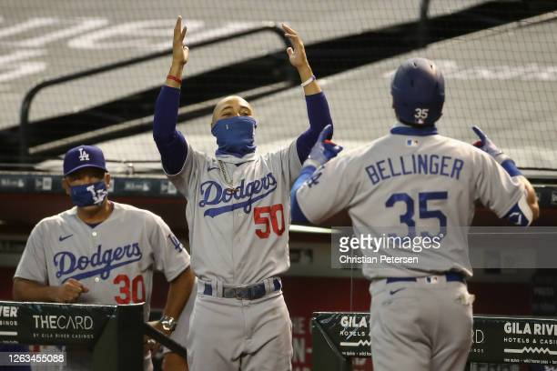 Mookie Betts and manager Dave Roberts of the Los Angeles Dodgers congratulate Cody Bellinger after Bellinger hit a two-run home run against the...