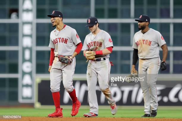 Mookie Betts, Andrew Benintendi, and Jackie Bradley Jr. #19 of the Boston Red Sox celebrate after defeating the Houston Astros 8-6 in Game Four of...
