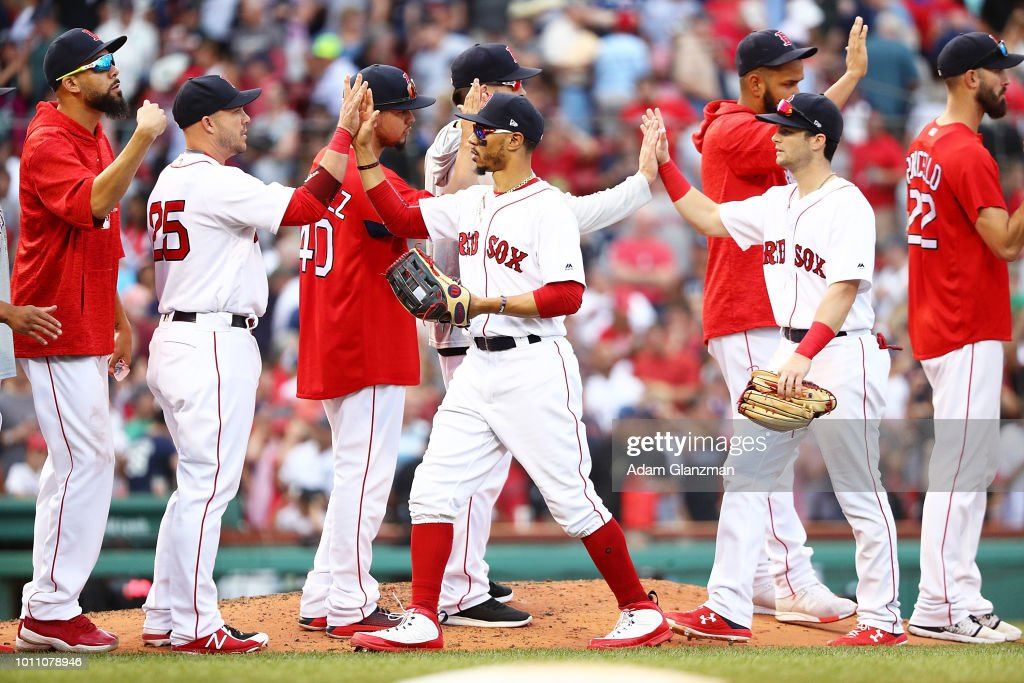 Mookie Betts #50, Andrew Benintendi #16, Steve Pearce #25, and David Price #24 of the Boston Red Sox high five each other after a victory over the New York Yankees at Fenway Park on August 4, 2018 in Boston, Massachusetts.