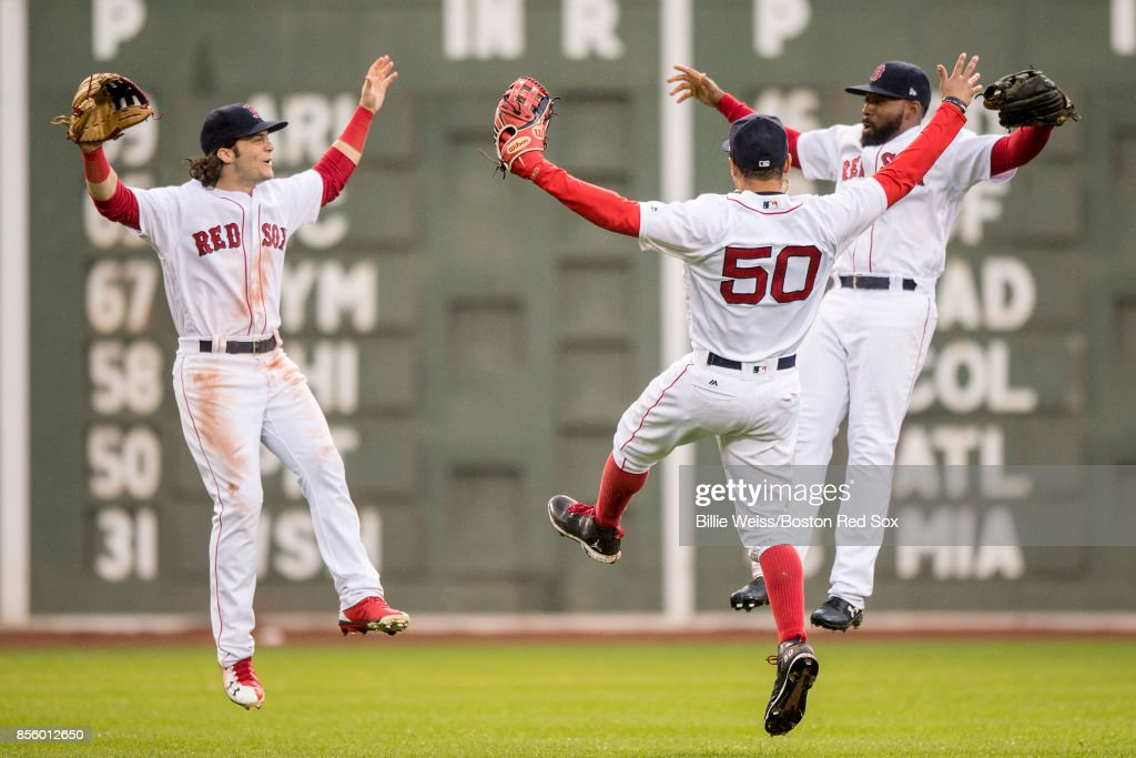 Mookie Betts #50, Andrew Benintendi #16,and Jackie Bradley Jr. #19 of the Boston Red Sox react after the final out was recorded to clinch the American League East Division against the Houston Astros on September 30, 2017 at Fenway Park in Boston, Massachusetts.