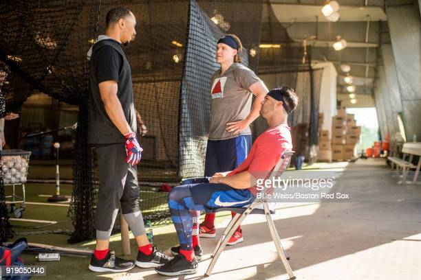 Mookie Betts Brock Holt and Andrew Benintendi of the Boston Red Sox talk in the batting cage during a team workout on February 16 2018 at Fenway...