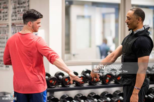 Mookie Betts high fives Andrew Benintendi of the Boston Red Sox in the weight room during a team workout on February 15 2018 at Fenway South in Fort...