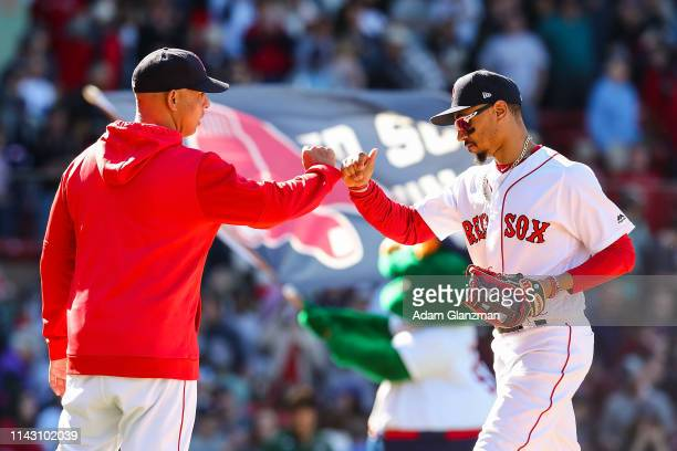 Mookie Betts high fives Manager lex Cora of the Boston Red Sox after defeating the Seattle Mariners at Fenway Park on May 11 2019 in Boston...