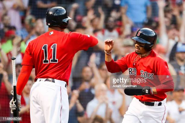 Mookie Betts high fives Rafael Devers of the Boston Red Sox after scoring In the fifth inning during game two of a double header against the Tampa...