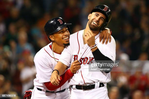 Mookie Betts hugs Deven Marrero of the Boston Red Sox after scoring in the sixth inning of a game against the Texas Rangers at Fenway Park on May 23...